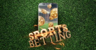 A phone with an image of gold coins its on articficial grass with the words, 'sports betting' draped across the bottom of the phone in gold lettering